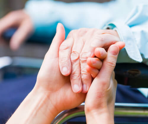 Close shot of senior in a wheel chair's hand being help by caregiver