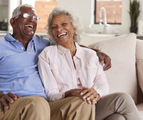 Senior Couple Sitting On Sofa At Home And Laughing Together
