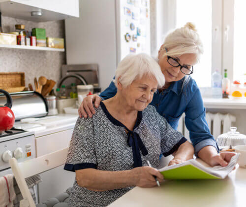 Woman and senior mother look over paperwork together at a kitchen table