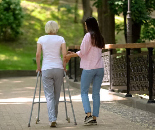 Woman with walker and young woman walking in a park